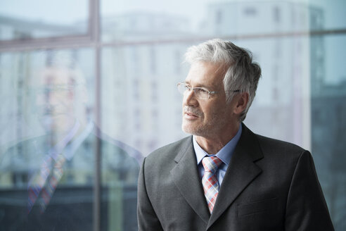 Businessman standing at window looking at distance - RBF002663