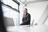 Businessman sitting on desk looking at distance - RBF002678