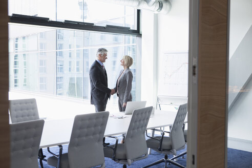 Businissman and businesswoman shaking hands in conference room - RBF002701