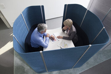 Businessman and businesswoman working in partitioned board room - RBF002731