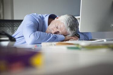Businessman sitting at desk, sleeping - RBF002741