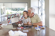 Grandfather and grandson building up a model airplane - ZEF004852