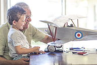 Grandfather and grandson building up a model airplane - ZEF004855