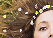 Woman lying on a meadow wearing daisies in her hair, close-up - GEMF000233