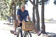 Smiling senior man balancing on bicycle - ZEF004746
