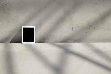Digital tablet on concrete floor - FMKF001555