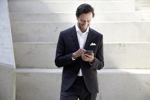 Businessman using smartphone in a modern building - FMKF001520