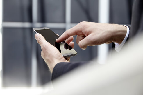 Hands of businessman touching screen of his smartphone - FMKF001523