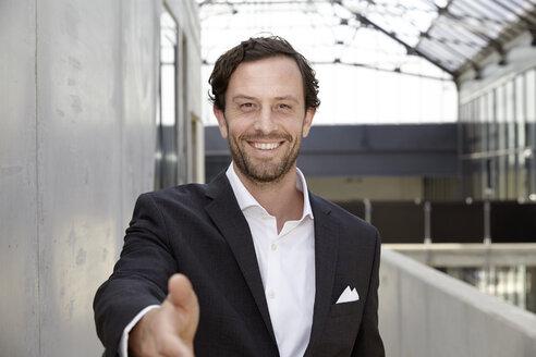Portrait of smiling businessman in a modern building - FMKF001534