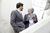 Two business people with digital tablet in modern architecture - FMKF001560