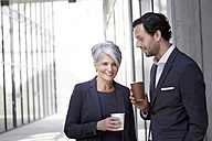 Two smiling business people with coffee to go - FMKF001538