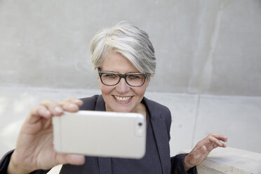 Portrait of smiling career woman taking a selfie with smartphone - FMKF001544