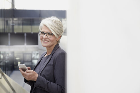 Portrait of smiling businesswoman with smartphone - FMKF001562