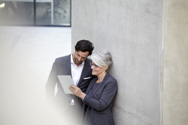 Two business people with digital tablet in modern architecture - FMKF001564