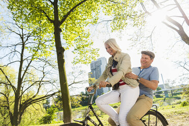 Mature couple riding bike in park, man sitting on rack - UUF004124