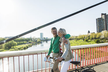 Germany, Mannheim, Mature couple crossing bridge, pushing bicycle - UUF004142