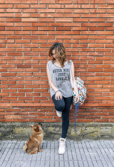 Young woman leaning against brick wall looking at Pomeranian puppy - MGOF000767