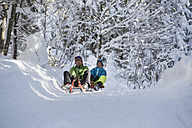 Germany, Bavaria, Inzell, couple having fun on sledges in snow-covered landscape - FFF001439