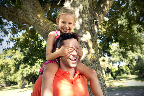 Smiling daughter on father's shoulders covering his eyes - TOYF000235