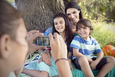 Girl taking picture of mother with children at tree - TOYF000248