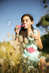 Girl blowing soap bubbles outdoors - TOYF000257