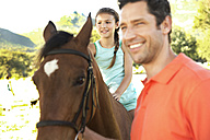 Father with smiling daughter sitting on horse - TOYF000260