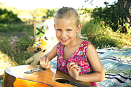 Smiling girl with guitar on blanket - TOYF000263