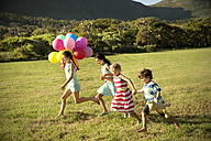 Happy children running with balloons on meadow - TOYF000266