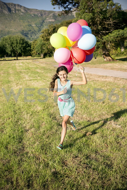 Happy girl running with balloons on meadow - TOYF000269