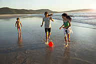 Three children playing with ball at the ocean - TOYF000294
