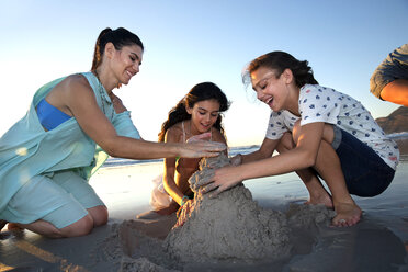 Mother and two daughters building a sand castle on the beach - TOYF000295