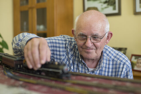 Portrait of smiling senior man with his model railway - RAEF000178