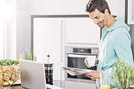 Man with cup of coffee reading newspaper in the kitchen - MADF000236