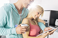 Couple using digital tablet in the kitchen - MADF000224