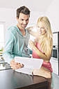 Couple using digital tablet in the kitchen - MADF000252