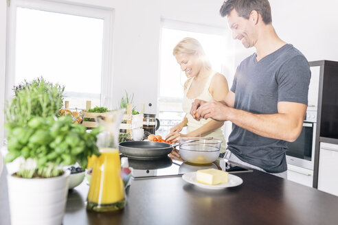 Couple preparing scrambled eggs together in the kitchen - MADF000225