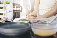 Couple preparing scrambled eggs together in the kitchen - MADF000257