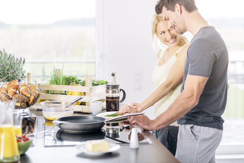 Couple preparing scrambled eggs together in the kitchen - MADF000258