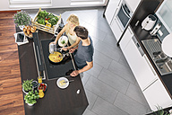 Couple preparing scrambled eggs together in the kitchen - MADF000259
