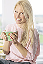 Portrait of smiling young woman with cup of coffee in the kitchen - MADF000278