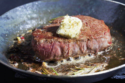 Fried fillet of beef with herb butter, peppercorns and rosemary in a pan - CSF025494