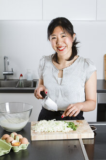 Portrait of smiling woman cutting spring onions in a kitchen - FLF001044