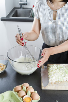 Woman stirring dough in a glassbowl with wire whisk - FLF001045