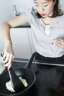 Woman preparing Okonomiyaki in a frying pan - FLF001047