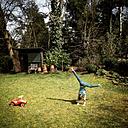 Girl turning wheels in garden - LV003424