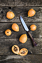 Sliced and whole medlars and a kitchen knife - SARF001764