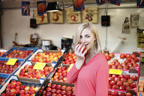 Smiling blond woman eating an apple in front of fruit stall on weekly market - RHF000822