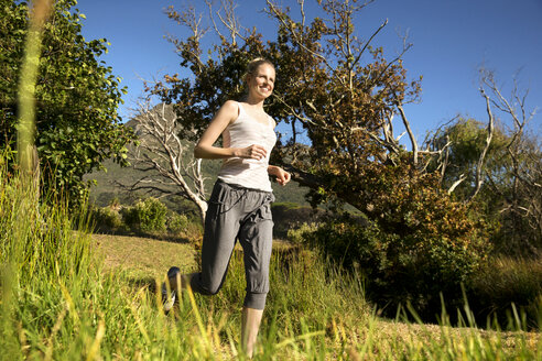 Smiling woman jogging in rural landscape - TOYF000333