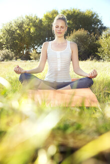 Woman practising yoga in a meadow - TOYF000342