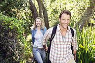 Smiling couple hiking hand in hand in forest - TOYF000399